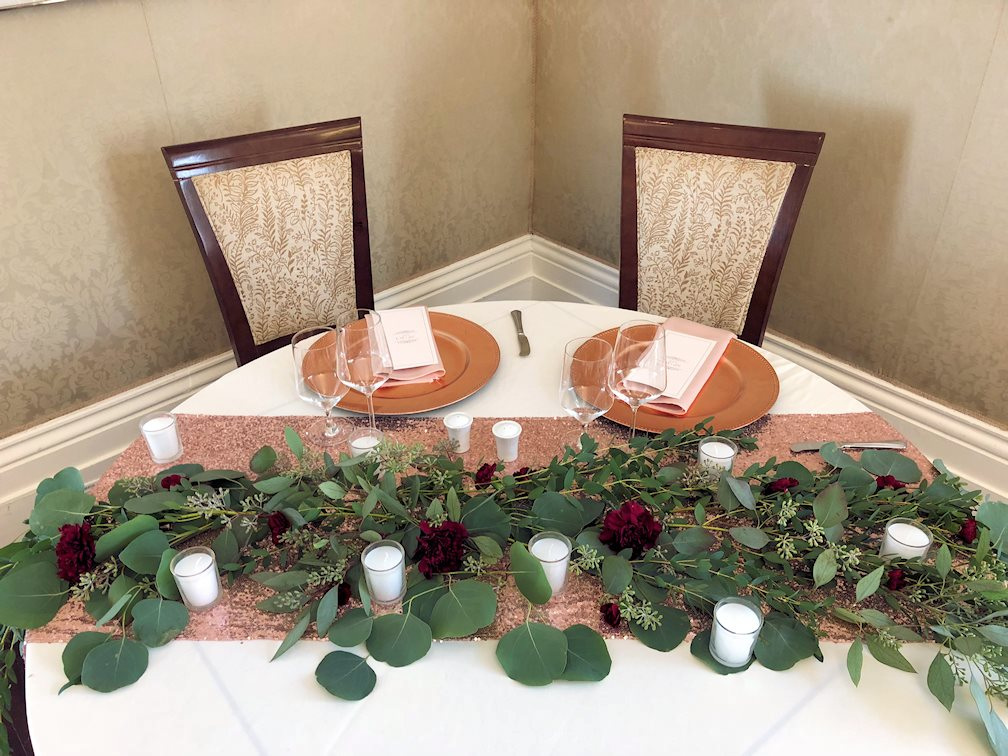 Chemin de table rose gold, centre de table verdure, roses et chandelles, sous-assiette rose gold